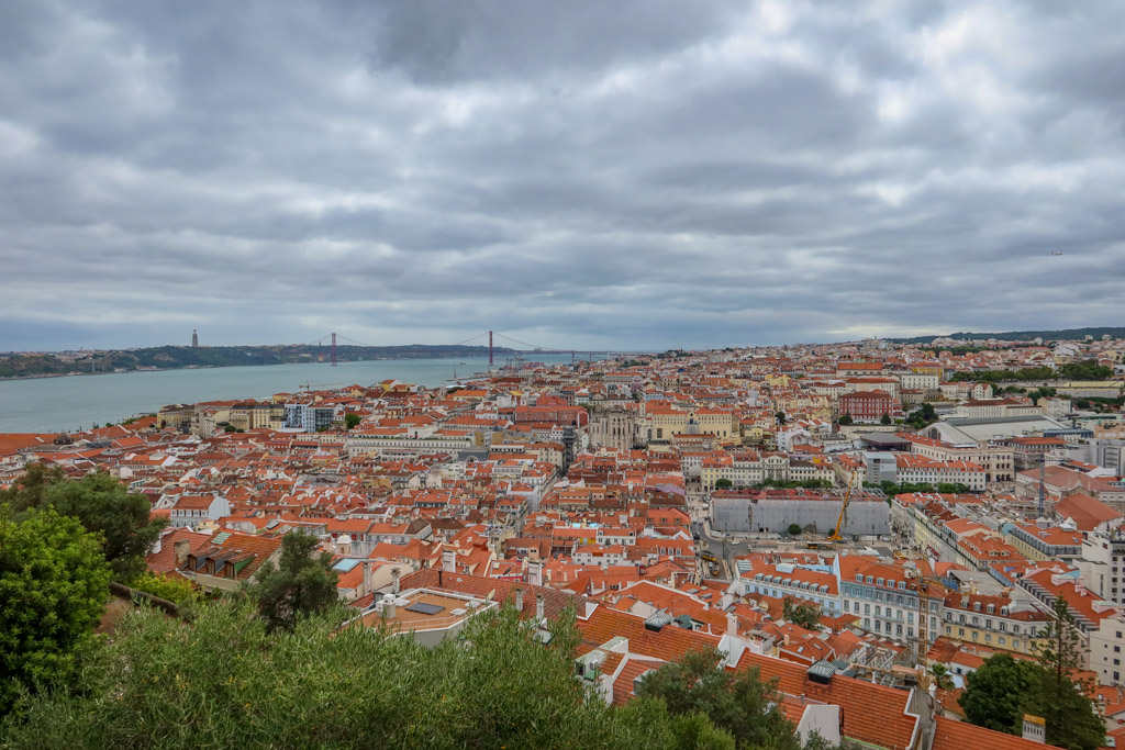 View of the city of Lisbon with many terra cotta tile roofs and the 25 de Abril Suspension Bridge in the distance