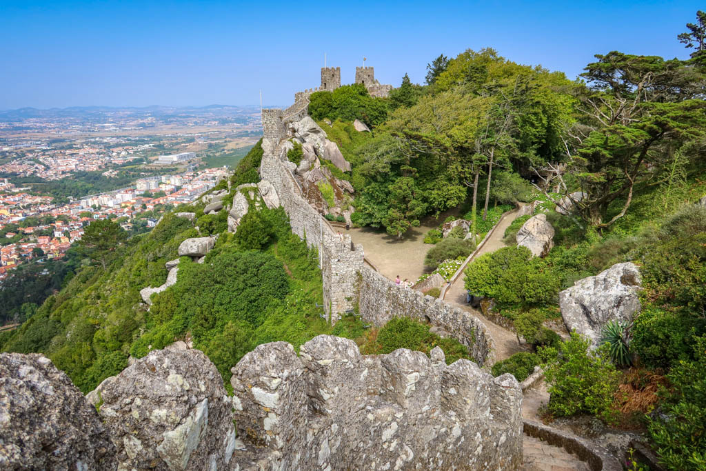 Old stone walls with turrets encircle the top of a hill overlooking Sintra