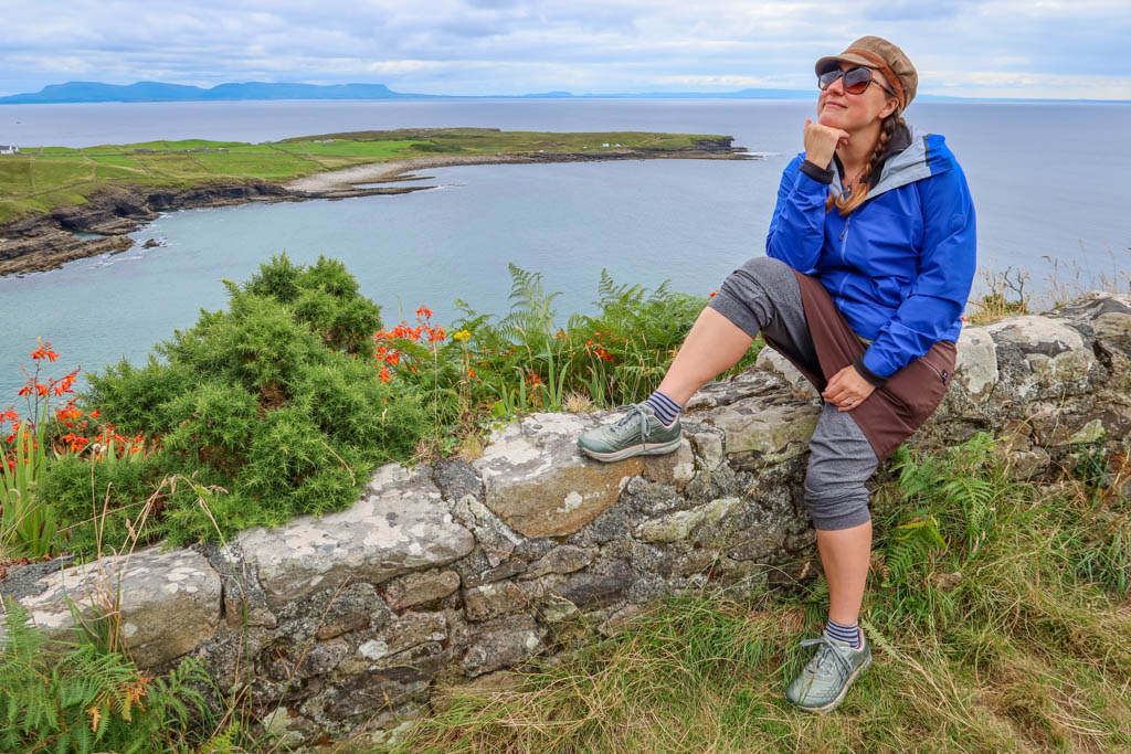 The author sits on a stone wall with an elbow propped awkwardly on her knee and a chin in her hand.