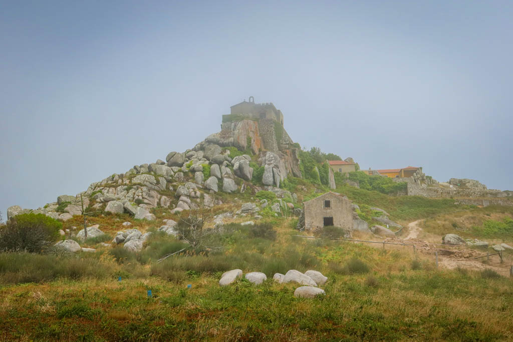 A historic stone church stands on a rocky knoll surrounded by fog