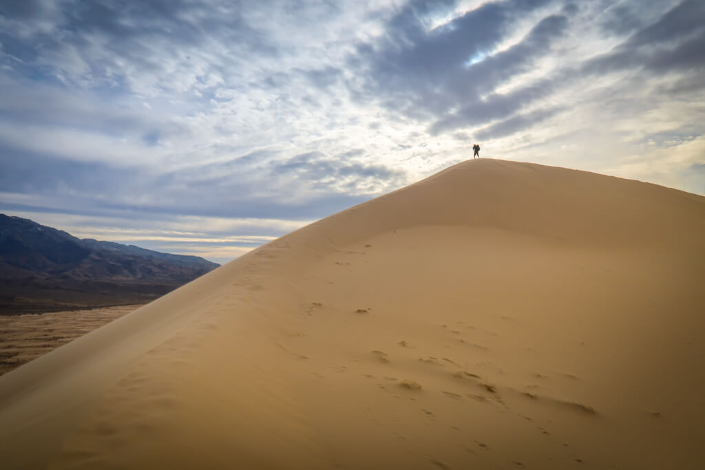 Silhouette of a photographer with a tripod taking a photo at the top of the dunes