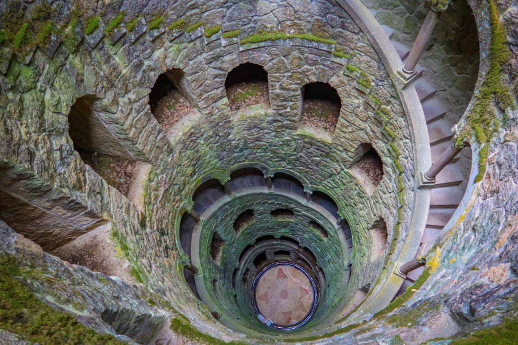 A spiral staircase leads down an inverted stone tower that is covered in green moss