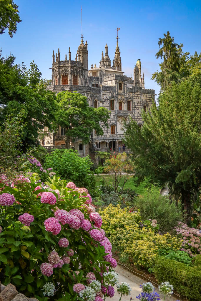 The gothic spires of Quinta da Regaleira stand behind a lovely garden filled with flowers