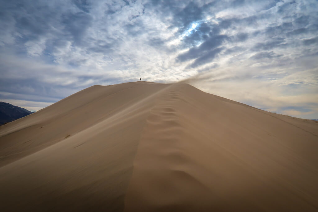 Nearing the summit of the Kelso Dunes. The trail traverses a sandy ridge with wind whipping sheets of sand off the trail.