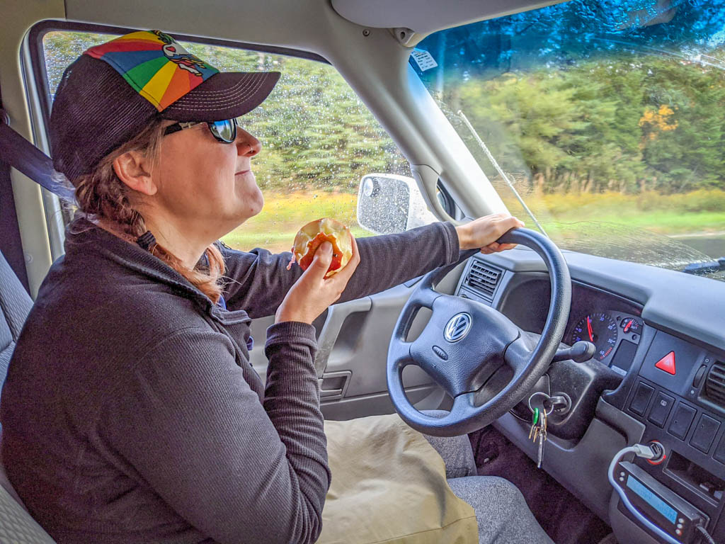 The author eats an apple while driving the motorhome