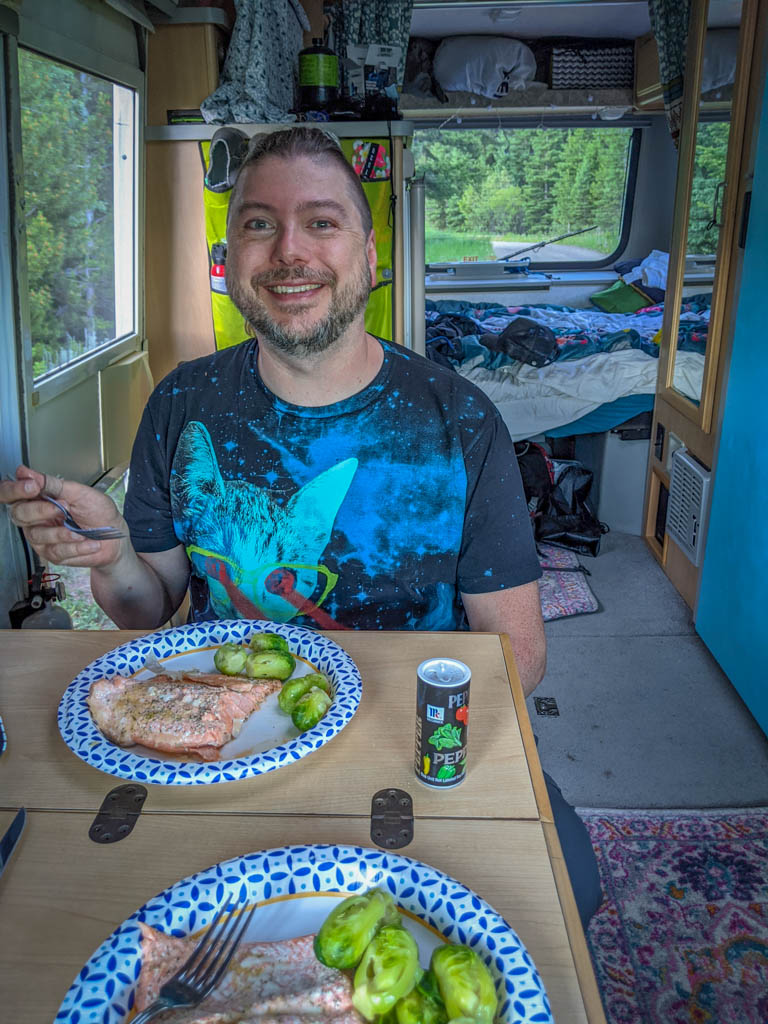 Daniel eats salmon and brussels sprouts inside the RV