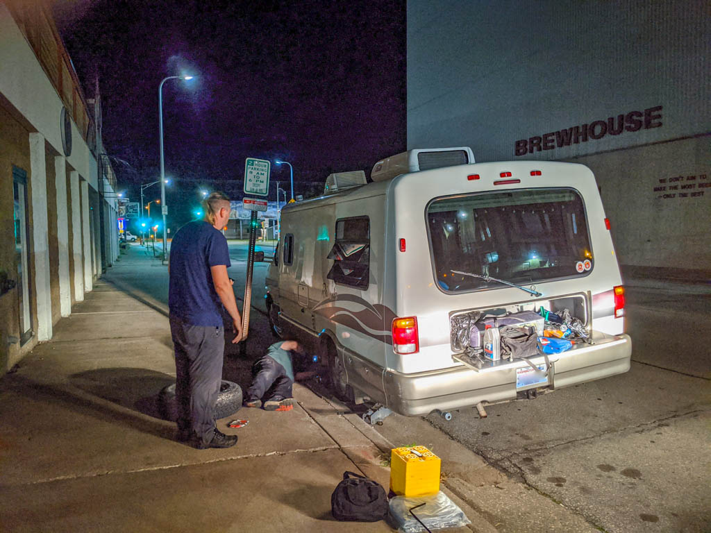 The Rialta is stranded on the side of a busy road at night while the tire is changed