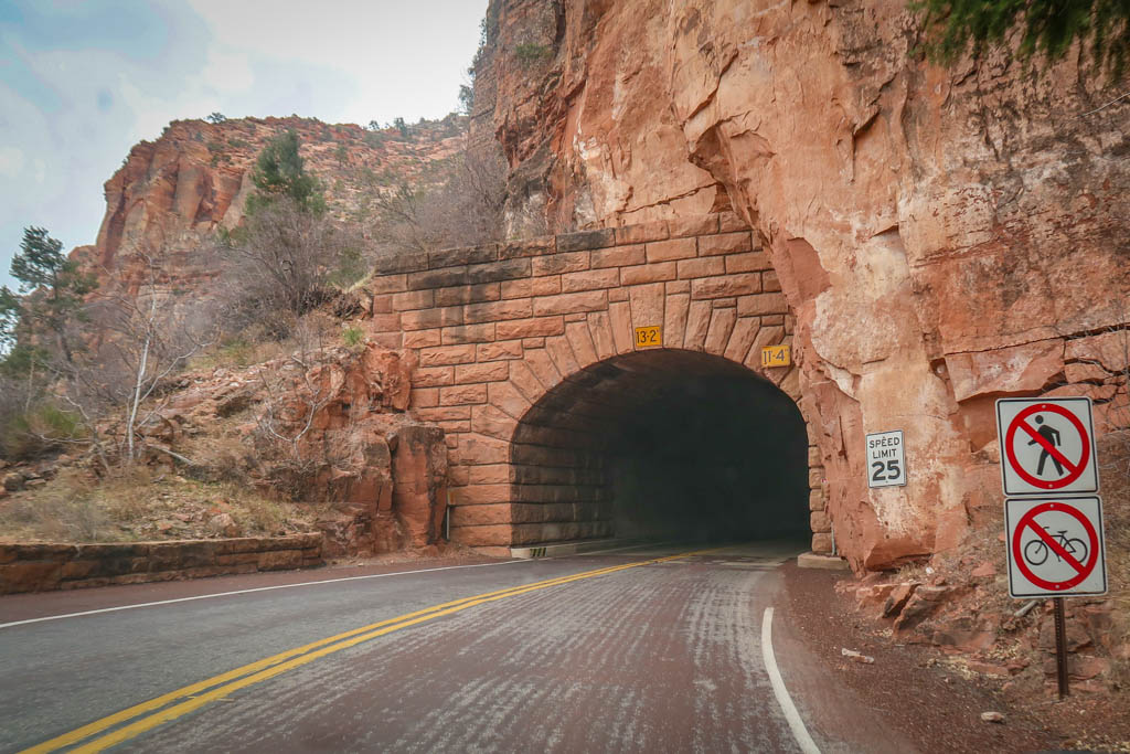 """The road enters to a tunnel blasted into the side of a cliff in Zion National Park. Maximum height of 13'2""""."""