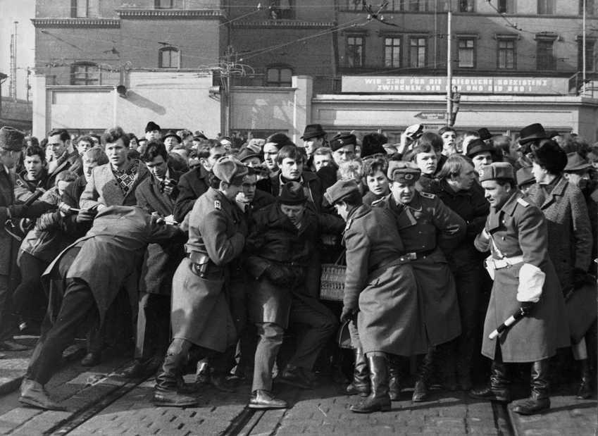 """Auf dem Platz zwischen dem Bahnhof und dem Interhotel """"Erfurter Hof"""" hat sich anlässlich des ersten innerdeutschen Gipfeltreffens zwischen Bundeskanzler Willy Brandt und DDR-Ministerpräsident Willi Stoph am 19. März 1970 in Erfurt eine Menschenmenge versammelt. Volksarmisten und in Zivil gekleidete Polizisten versuchten, die Schaulustigen zurückzudrängen."""