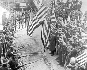 Streikende in Lawrence, Massachusetts mit US-Fahnen werden von der Nationalgarde bedroht. Rote Fahnen und andere Embleme der Arbeiterbewegung waren verboten, aber auch die Stars and stripes boten keinen Schutz.