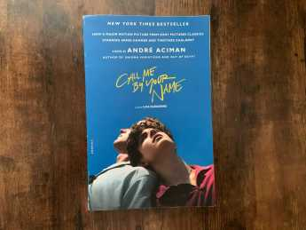 """Photo of the book """"Call Me By Your Name"""" on a table."""