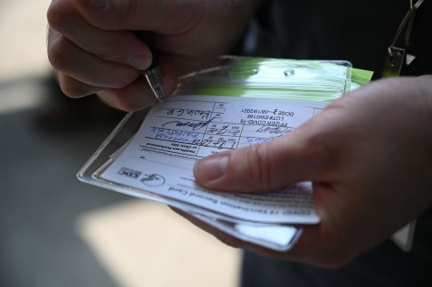 A nurse marks a coronavirus vaccination card. (Robyn Beck/AFP/Getty Images/TNS)