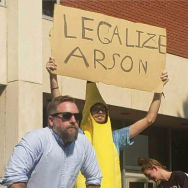 """Student holding a sign that read """"legalize arson"""" standing behind """"campus preacher"""" Keith Darrell."""