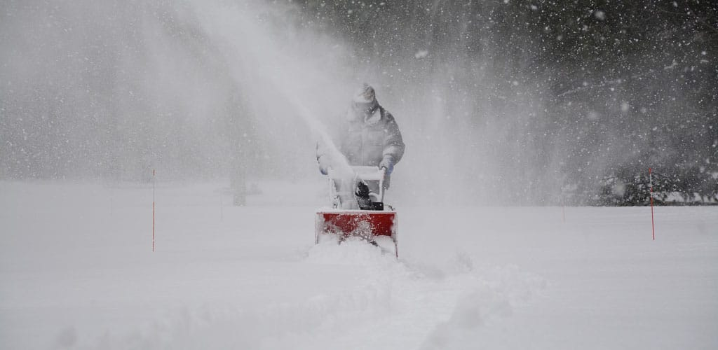 A man uses a snowblower to clear snow off of a driveway