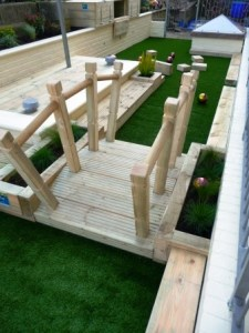 Timber play bridge with artificial turf surround