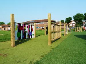 Coloured playground sensory screen with wooden climbing bars in foreground