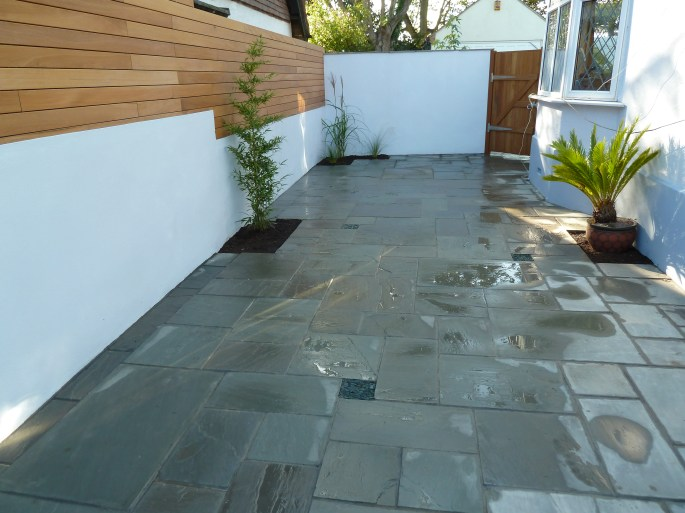 Courtyard dining area with paving, specimen planting and wall with hardwood screen
