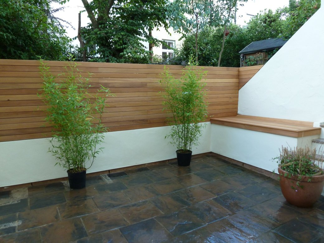 Arbworx signature vertical hardwood decking screen with block paving and ornamental bamboo pots