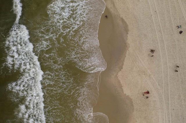 Unas pocas personas en la playa de Arpoador en Rio de Janeiro, Brasil.
