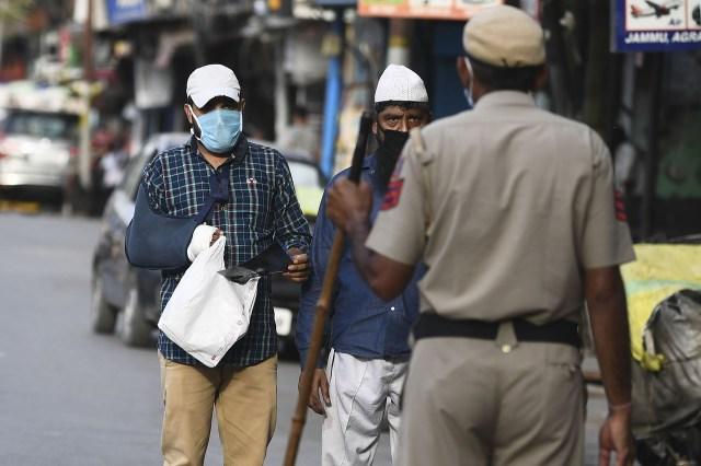 Un oficial de policía interroga a peatones en un puesto de control en el casco antiguo de Nueva Delhi el 23 de abril de 2020. (Foto de SAJJAD HUSSAIN / AFP)