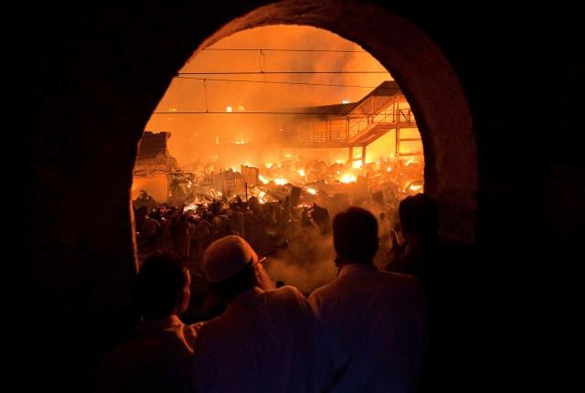 La gente observa desde un edificio cercano mientras un incendio arde en un barrio bajo de Mumbai, India, el 4 de marzo de 2011 (REUTERS/Vivek Prakash)