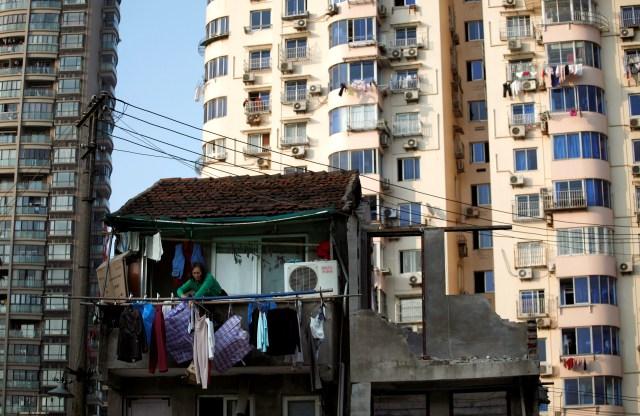 Una mujer se para en el balcón de su casa que será demolida para construir nuevos apartamentos en el centro de Shanghai, China, el 1 de diciembre de 2010 (REUTERS/Carlos Barria)