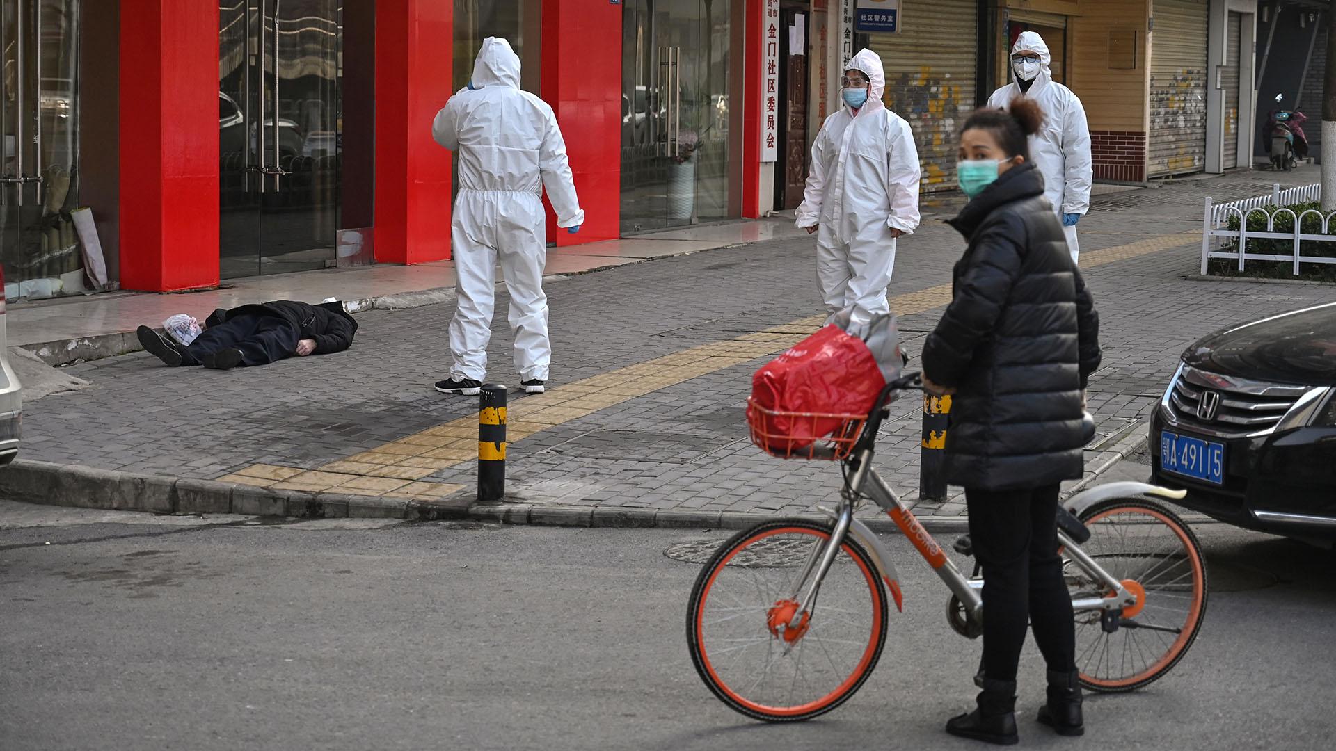 Un anciano con una máscara facial murió en una calle cercana a un hospital en Wuhan (Héctor RETAMAL / AFP)