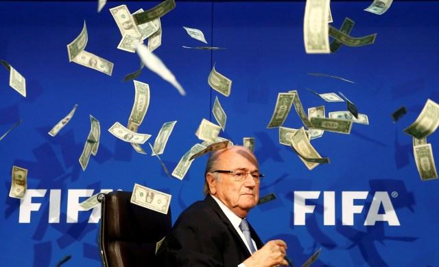 El cómico británico conocido como Lee Nelson arroja billetes al entonces Presidente de la FIFA, Joseph Blatter, cuando llega a una conferencia de prensa tras la reunión extraordinaria del Comité Ejecutivo de la FIFA en la sede de la FIFA en Zúrich, Suiza, el 20 de julio de 2015 (REUTERS/Arnd Wiegmann)