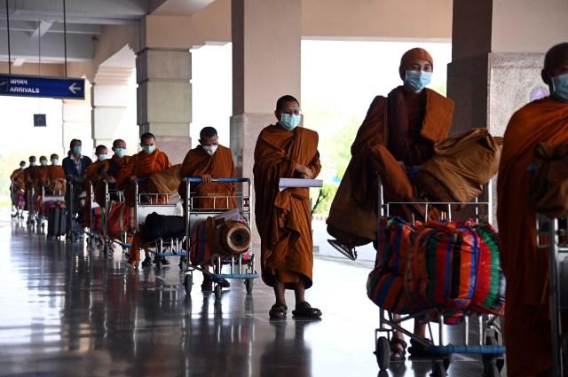 Monjes budistas de nacionalidad tailandesa hacen cola antes de facturar un vuelo con destino a Tailandia durante la cuarentena en el aeropuerto internacional de Gaya, a unos 5 km de Bodhgaya, el 24 de abril de 2020. (Foto de SUMAN / AFP)