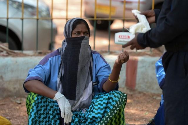 Un barrendero recibe guantes distribuidos por la Dirección de la Unidad Médica y de Salud en Hyderabad el 22 de abril de 2020. (Foto de NOAH SEELAM / AFP)