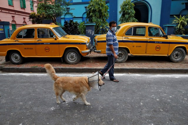 Un hombre con una máscara pasea a su perro con un collar isabelino, un dispositivo de protección para evitar que se lama el cuerpo, en Calcuta, India, el 24 de abril de 2020. REUTERS/Rupak De Chowdhuri