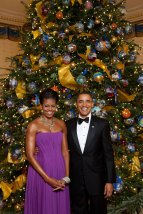 First Lady Michelle Obama and President Barack Obama posing in front of the White House Christmas tree,