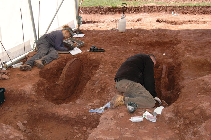 Two archaeologists excavating within a trench. Recent excavation of the Pembrokeshire chariot burial, first discovered last year, revealed the tyres of the chariot. [Photo credit: Amgueddfa Cymru – National Museum Wales]