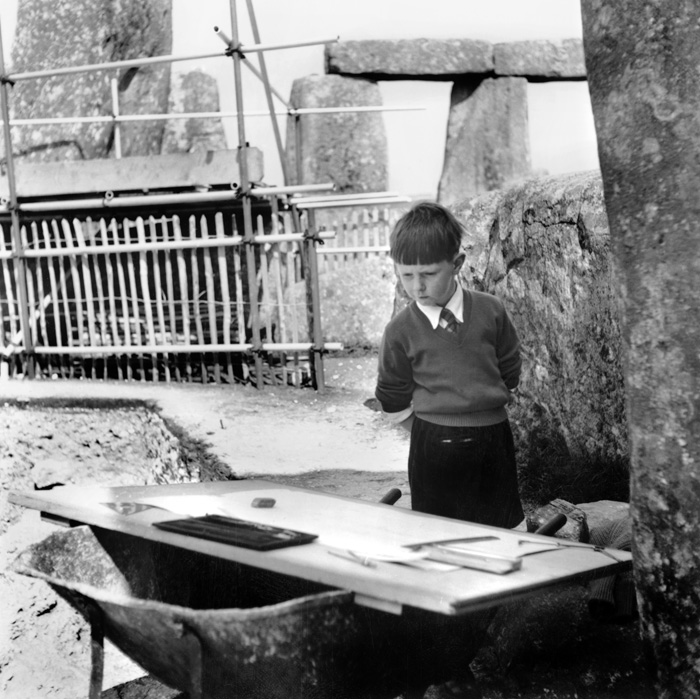 A young boy looking at archaeological plans laid out on top of a wheelbarrow in the middle of Stonehenge