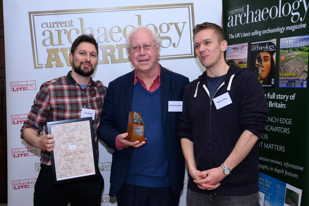 Tom Brindle, Michael Fulford, and Martyn Allen, some of the author of Life and death in the countryside of Roman Britain, collect the award for Book of the Year 2020 at the Current Archaeology Awards.