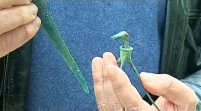 Prof. Nikolay Ovcharov shows the two Late Bronze Age Ancient Thracian artifacts, the Thracian sacrifice ritual knife and the bronze toy stork - which have made their way to the Bulgarian archaeologists after they were acquired by a private collector from Zlatograd, Southern Bulgaria. Photo: TV grab from BNT