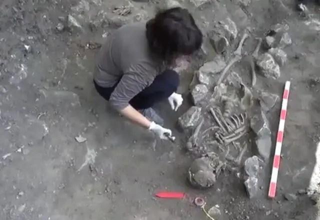 Archaeologist Alexandra Petrova shows the newly discovered human skeleton at the Vratitsa (Gradishte) Fortress near Bulgaria's Vratsa. Photo: TV grab from Konkurent TV