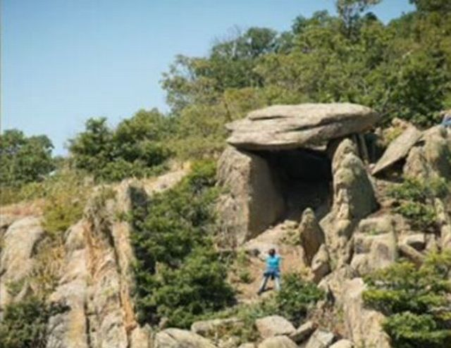 """The newly discovered dolmen - a prehistoric or early ancient single-chamber stone tomb - near Zlatosel in the Sredna Gora Mountain in Southern Bulgaria. It is said to be the largest dolmen found in Bulgaria to date, the size of a """"two-room apartment"""". Photo: TV grab from BNT"""