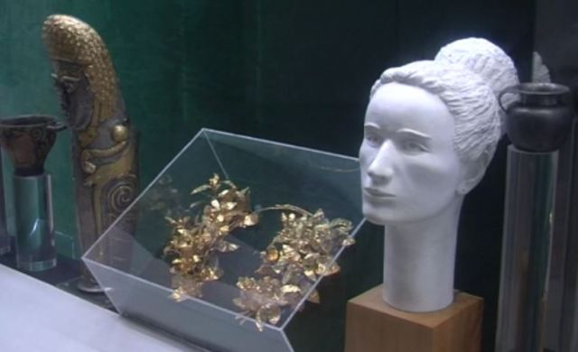 A view of part of the artifacts from the Mogilanska Mound Treasure (the Vratsa Gold Treasure) as displayed in the Regional Museum of History in Bulgaria's Vratsa - the golden laurel wreath and a model reconstruction of the face of the Ancient Thracian princess from the Triballi tribe who wore it; and the gold-plated silver royal greave. Photo: TV grab from BNT 2
