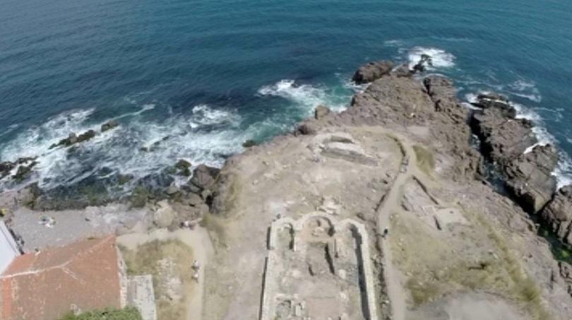 An aerial shot of the rocky Cape Stolets in Bulgaria's Sozopol showing the ruins of the 12th century Christian basilica in the foreground, with the ruins of the 6th century BC Ancient Greek shrine, and the 6th AD Byzantine fortress tower in the background. Photo: TV grab from BNT