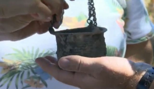 A well-preserved bronze candelabrum with a cross discovered in Novae during the 2016 digs. Photo: TV grab from the Bulgarian National Television