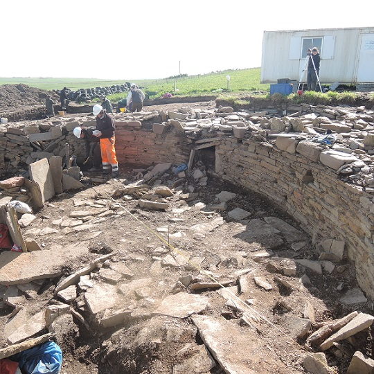 Woody and Alex recording the rough paving and organic deposits inside the western half of the broch