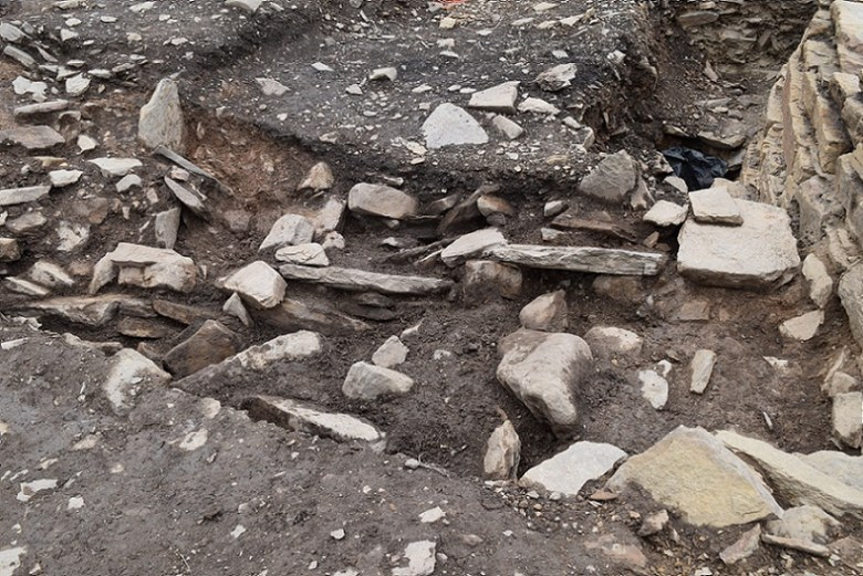 The top of the revetment wall emerges in the broch terrace cut