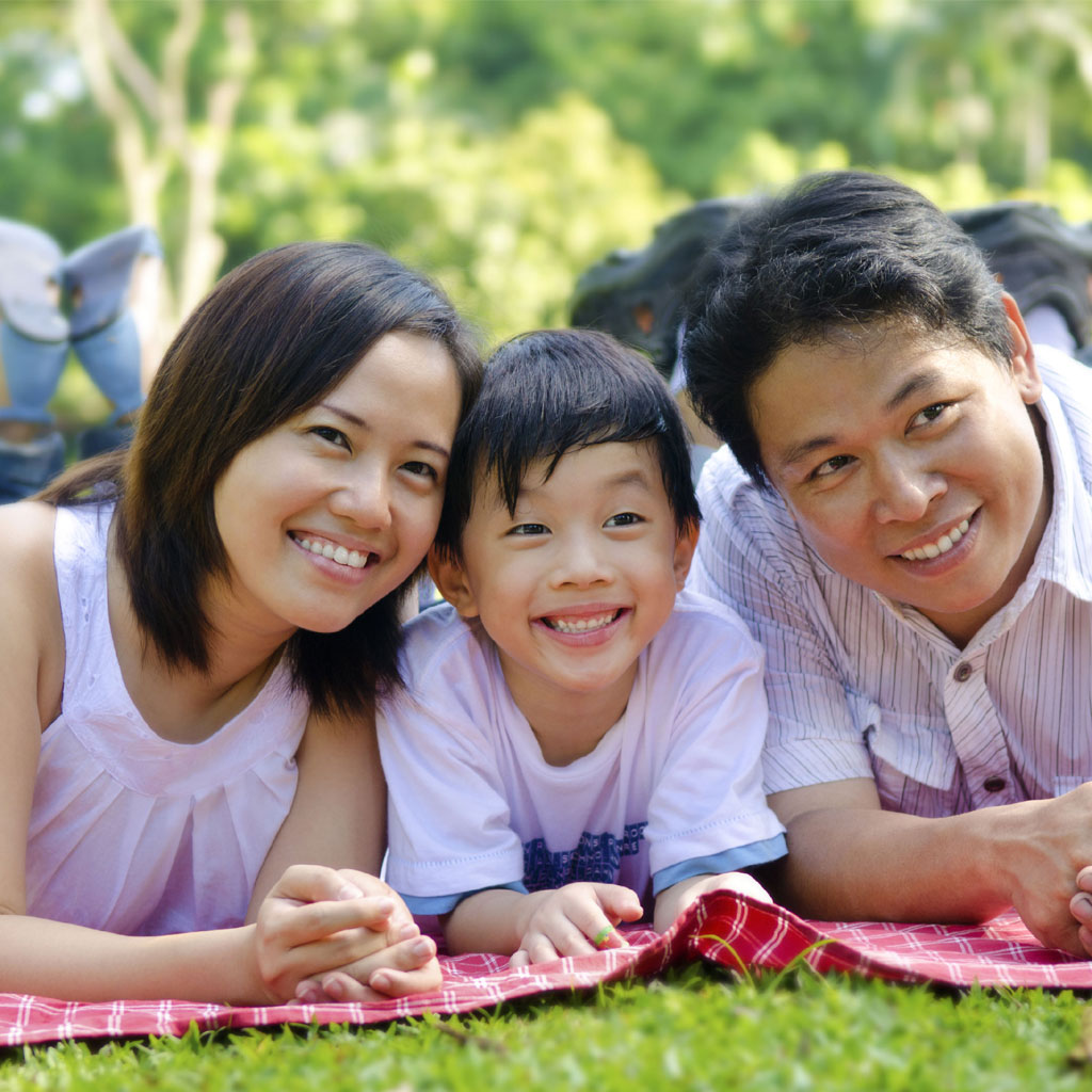 Smiling family laying on picnic blanket