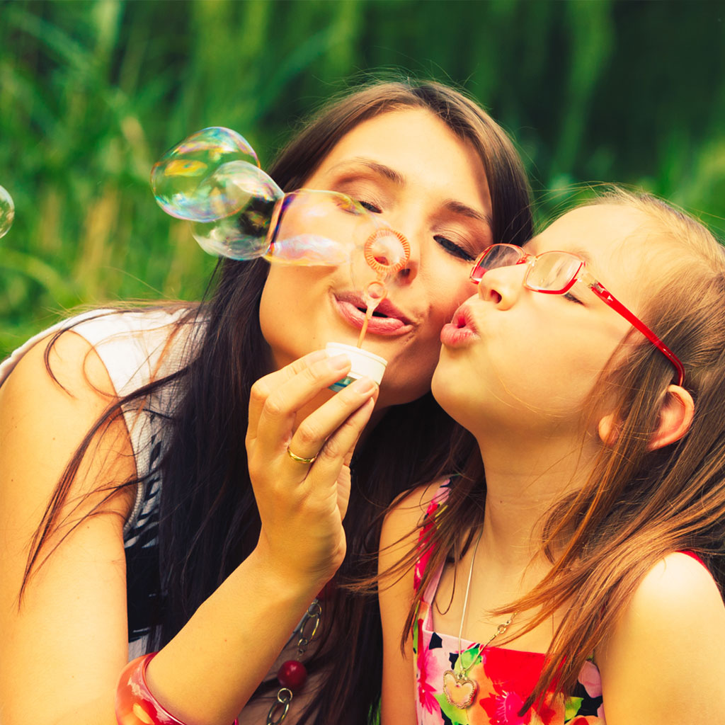 Mother blowing bubbles with daughter