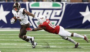 BGSU's Ronnie Moore stiff arms a diving Northern Illinois defender. Photo via BGSU Marketing and Communications.