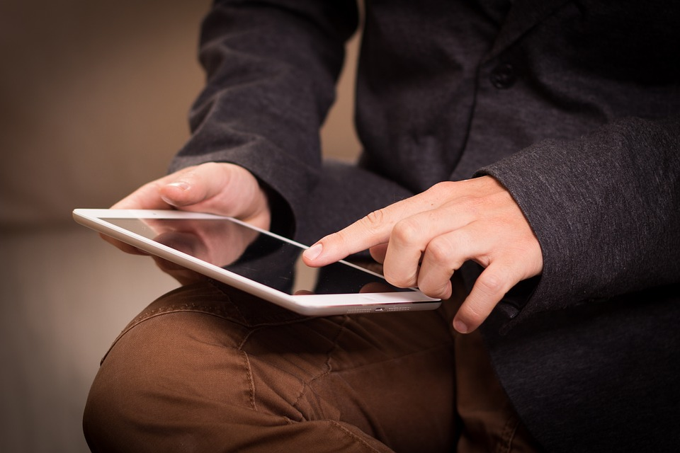 Man holding tablet swipes on screen