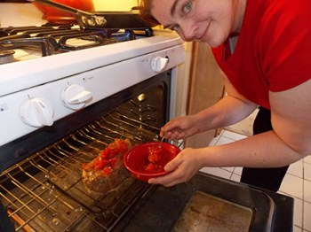 Jennifer Laske spreads canned tomatoes on the meatloaf before it heads into the oven.