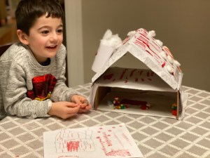 A young boy smiling next to his holiday elf house project