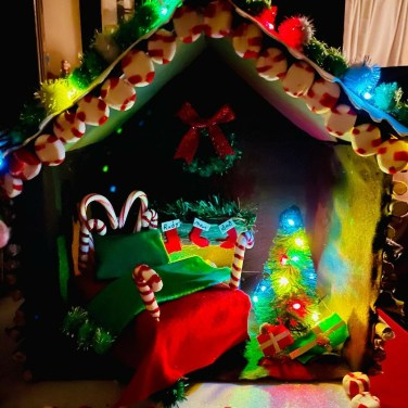 a miniature log cabin festive elf house project complete with candy cane headboard bed, blanket and hearth